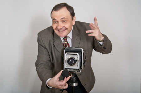 aims: Cheerful man in jacket and tie aims retro photo camera and opens lens for shooting.