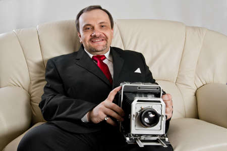 Cheerful man in black suit and red tie with vintage camera.