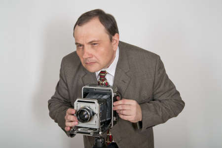 Man in jacket and tie aiming retro photo camera.