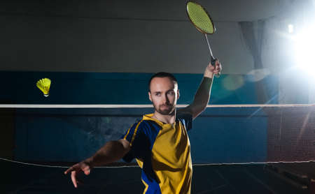 Bearded  badminton player in sport outfit making a racket swing. Artistic studio lighting and lens flare effect. 版權商用圖片 - 59840610