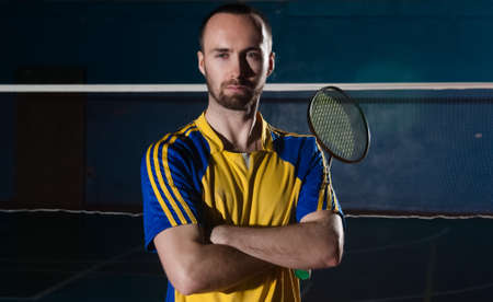 sportsperson: Bearded  badminton player in sport outfit holds racket. Artistic studio lighting and lens flare effect.