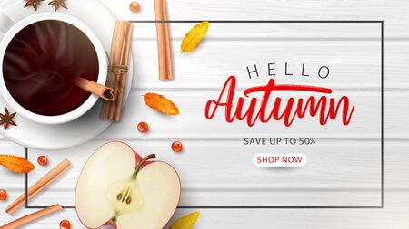 Autumn sale advertisement banner. Top view on composition with coffee cup, sliced apple, rowan berries and leaves and cinnamon sticks on wooden texture.