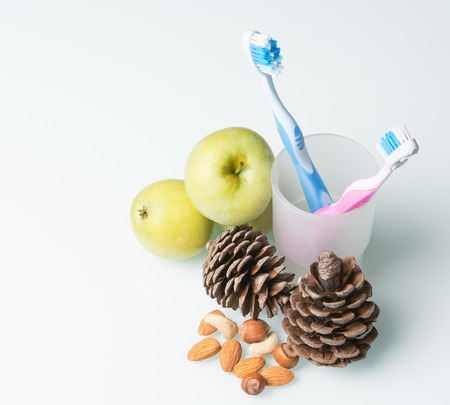 two colorful toothbrushes in a glass beaker with cones and apples Imagens