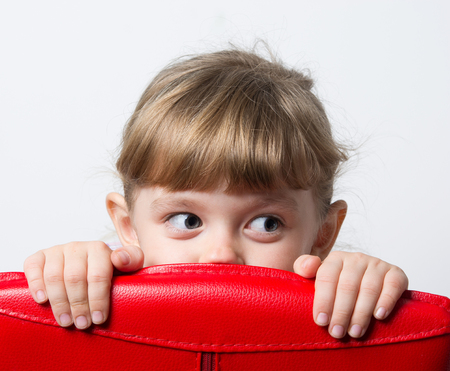 girl hiding behind the red chair