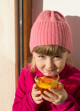 little girl warms his hands on a Cup of tea