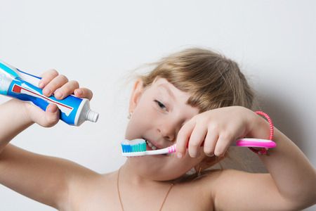 pushes: little girl squeezing toothpaste on the brush