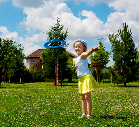 child plays on a green meadow and a Sunny day