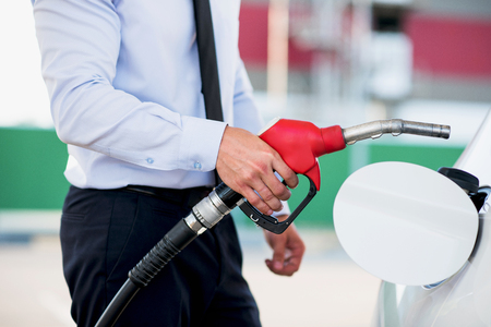 fuelling pump: process of refueling the white car with petrol