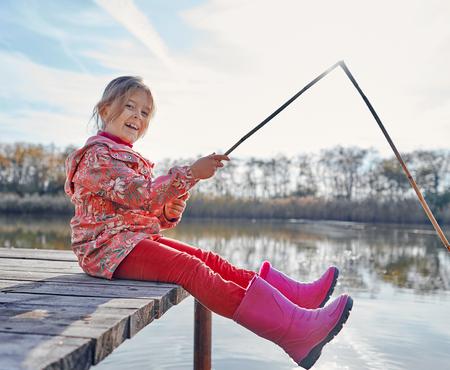 bambina che pesca sul fiume