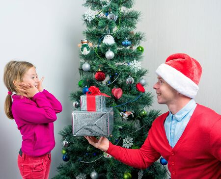Santa Claus gives a gift under the Christmas tree girl Stock Photo