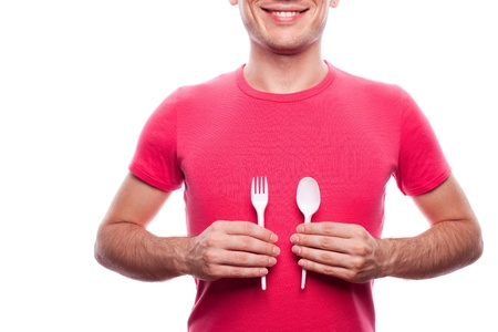 smiling handsome guy holding plastic fork and spoon near his stomach over white background  studio shot  photo