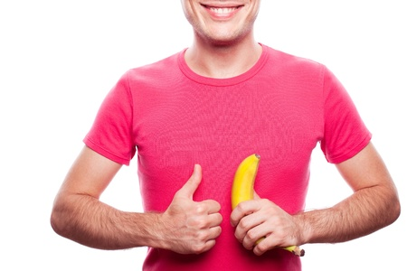smiling handsome guy holding yellow banana and showing ok  thumb up  near his stomach over white background  studio shot  photo