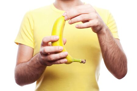 guy holding and opening yellow banana over white background  studio shot  photo
