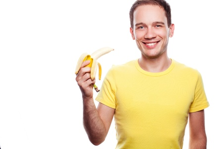 smiling handsome guy holding yellow banana over white background. studio shot. photo