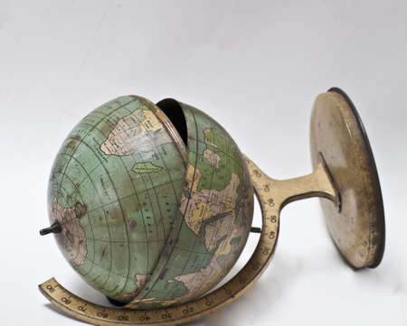 end times: Vintage metal world globe lies cracked and broken Stock Photo