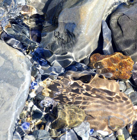 water stained: Incoming tide covers colorful rocks and creates jewel tones Stock Photo
