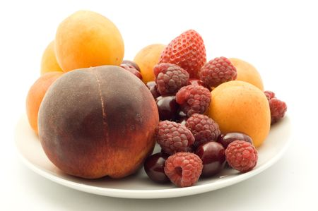 Apricots, strawberry peach and cherries on plate on the white background