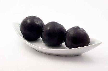Fresh ripe plum on a plate on a white background 版權商用圖片