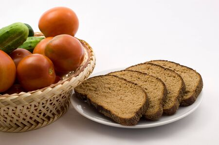 Tomatoes and cucumbers in a plate of rice straw and bread on a plate on a white background