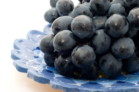 Bunch of ripe black grapes on a plate on a white background closeup