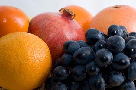 Citrus fruit (bananen, kaki, grapefruit, Mandarijn, oranje, granaatappel, druiven) op een witte achtergrond close-up