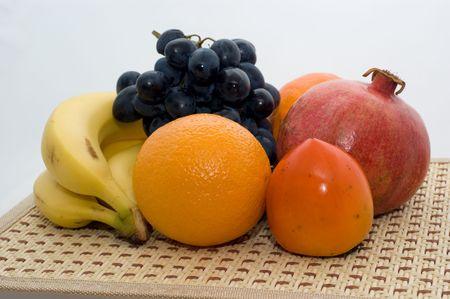 Citrusvruchten (banaan, persimmon, grapefruit, mandarijn, sinaasappel, granaatappel, druiven) op een witte achtergrond close-up