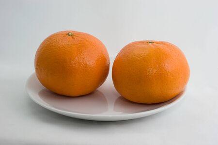 Mandarins op een plaat op een witte close-up als achtergrond