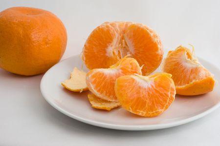 Ontruimde mandarin op een plaat op een witte close-up als achtergrond Stockfoto - 8096896