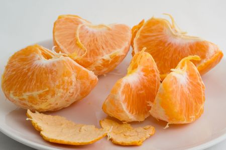 cleared: Cleared mandarin on a plate on a white background closeup