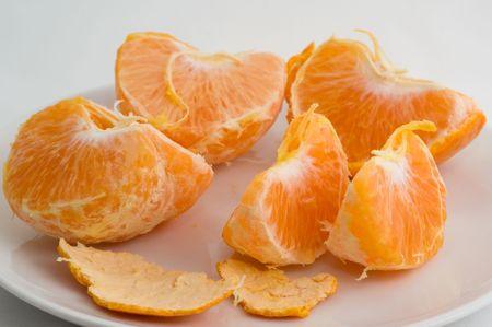 Ontruimde mandarin op een plaat op een witte close-up als achtergrond