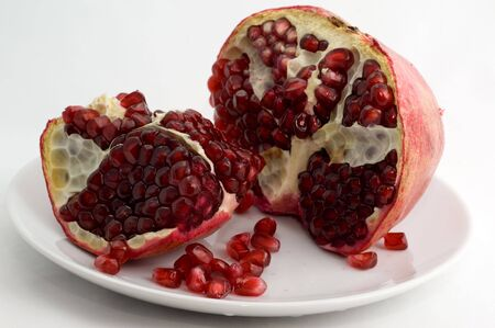 Half-cleared pomegranate on a plate on a white background closeup Stok Fotoğraf