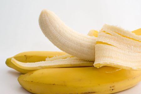 Bananen en één helft-ontruimde banaan op een witte close-up als achtergrond Stockfoto