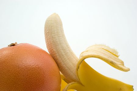 Half-cleared banana and grapefruit on a white background closeup Stockfoto