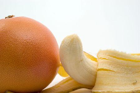 Half-ontruimde banaan en grapefruit op een witte close-up als achtergrond Stockfoto - 8096901