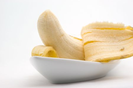 Half-cleared banana on a plate on a white background closeup