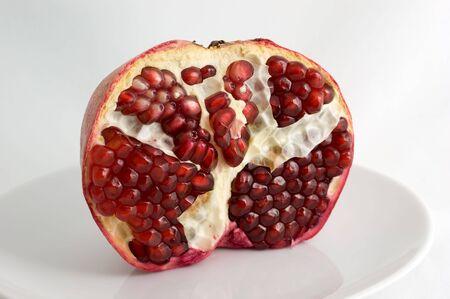 Half-ontruimde granaatappel op een plaat op een witte close-up als achtergrond