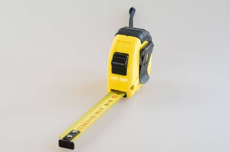 Yellow plastic tape measure on a white background close-up