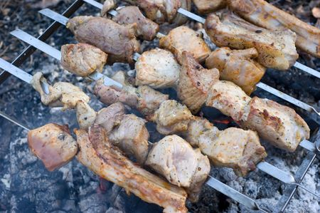 Peaces of meat on skewers and they are fried like stringed on hot coals Фото со стока