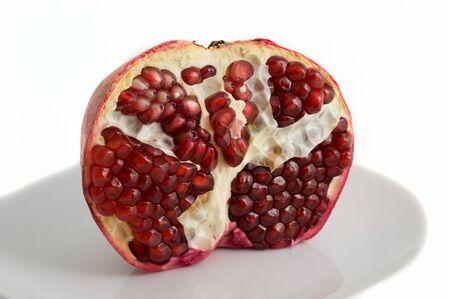Half-ontruimde granaatappel op een plaat op een witte close-up als achtergrond Stockfoto - 8293727