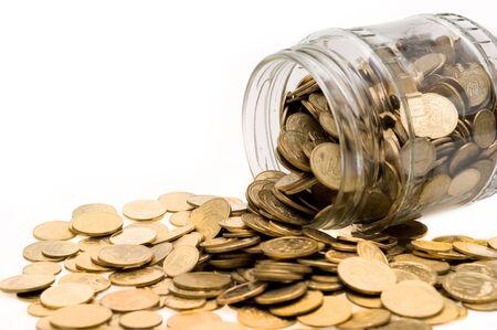 Ukrainian coins spill abundantly from glass banks on white background closeup Banco de Imagens