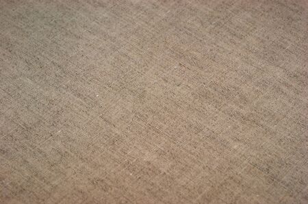 The background of textured bright linen fabric closeup