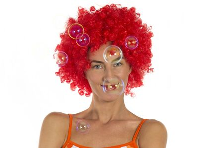 eyelids: A young beautiful woman in an orange wig with soap bubbles in the air on a white background.  Stock Photo