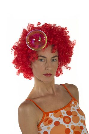 A young beautiful woman in an orange wig with soap bubbles in the air on a white background.  Imagens