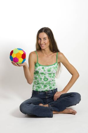 eyelids: A young beautiful woman holding a ball on a white background