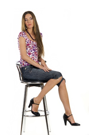 Portrait of a  beautiful girl sits on the bar stool on a white background closeup Stock Photo - 10575024