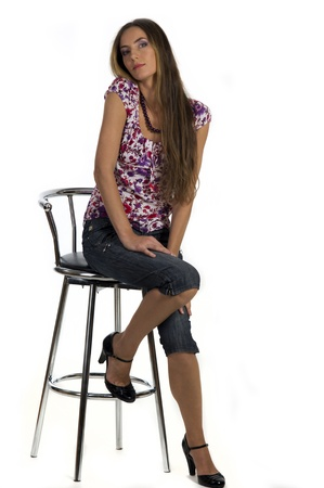 Portrait of a  beautiful girl sits on the bar stool on a white background closeup Stock Photo - 10608538