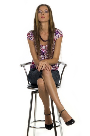 stool: Portrait of a  beautiful girl sits on the bar stool on a white background closeup