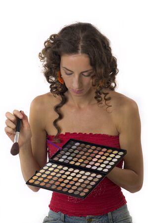 Schattig meisje met prachtige lange haren maakt make-up op een witte achtergrond close-up