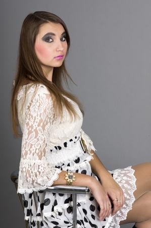 美しい少女の肖像画は、バーに座っている灰色の背景のクローズ アップのスツール 写真素材