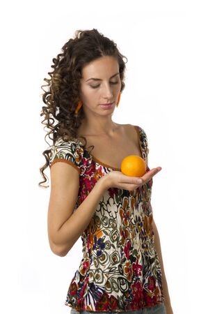 belle: Portrait of a cute girl with beautiful long hair with an orange in your hands on a white background closeup Stock Photo
